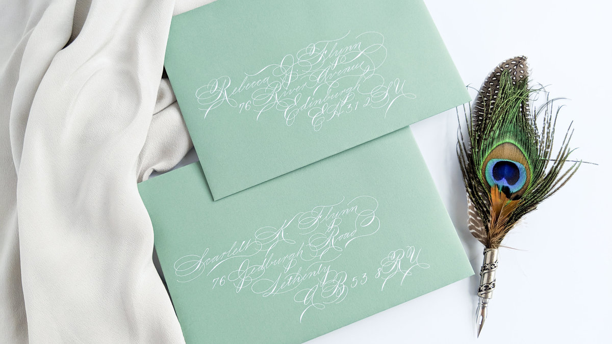 Spencerian envelope calligraphy with white ink on light green envelopes