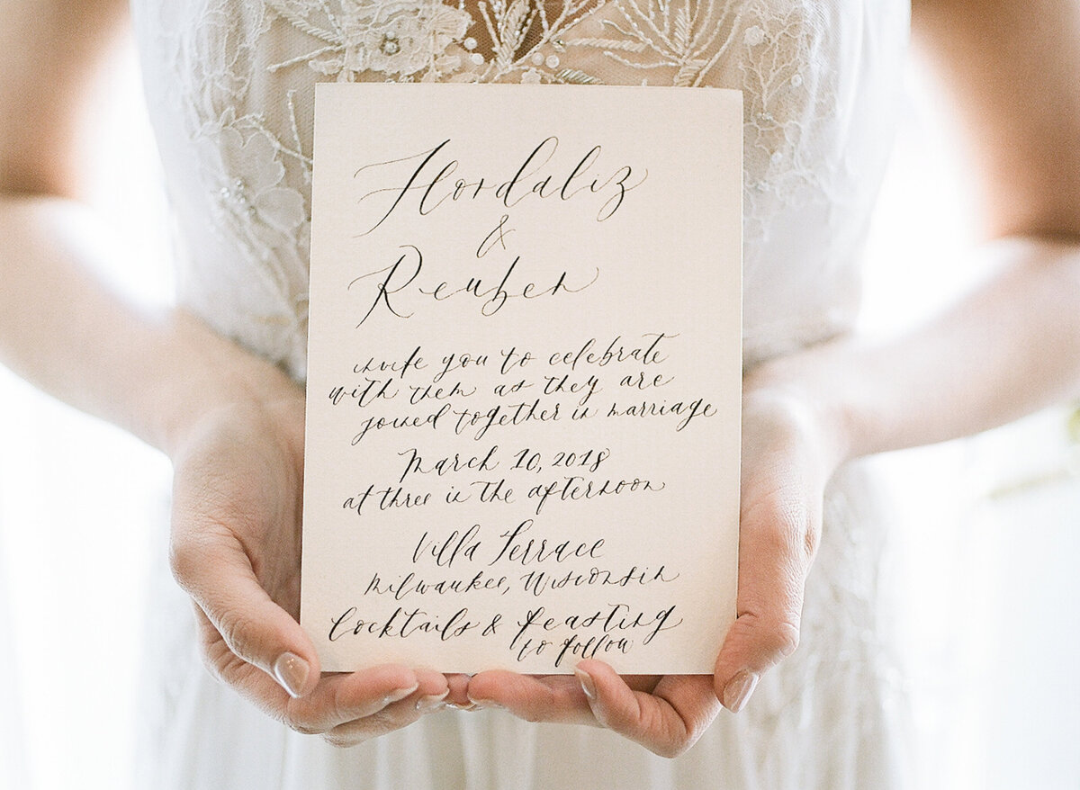 Bride holding invitation for destination wedding