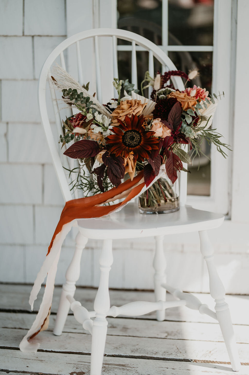 brides flower bouquet sitting on a white chair