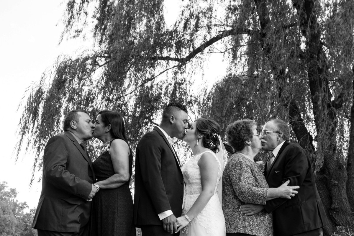 couple and both sets of parents kiss picture