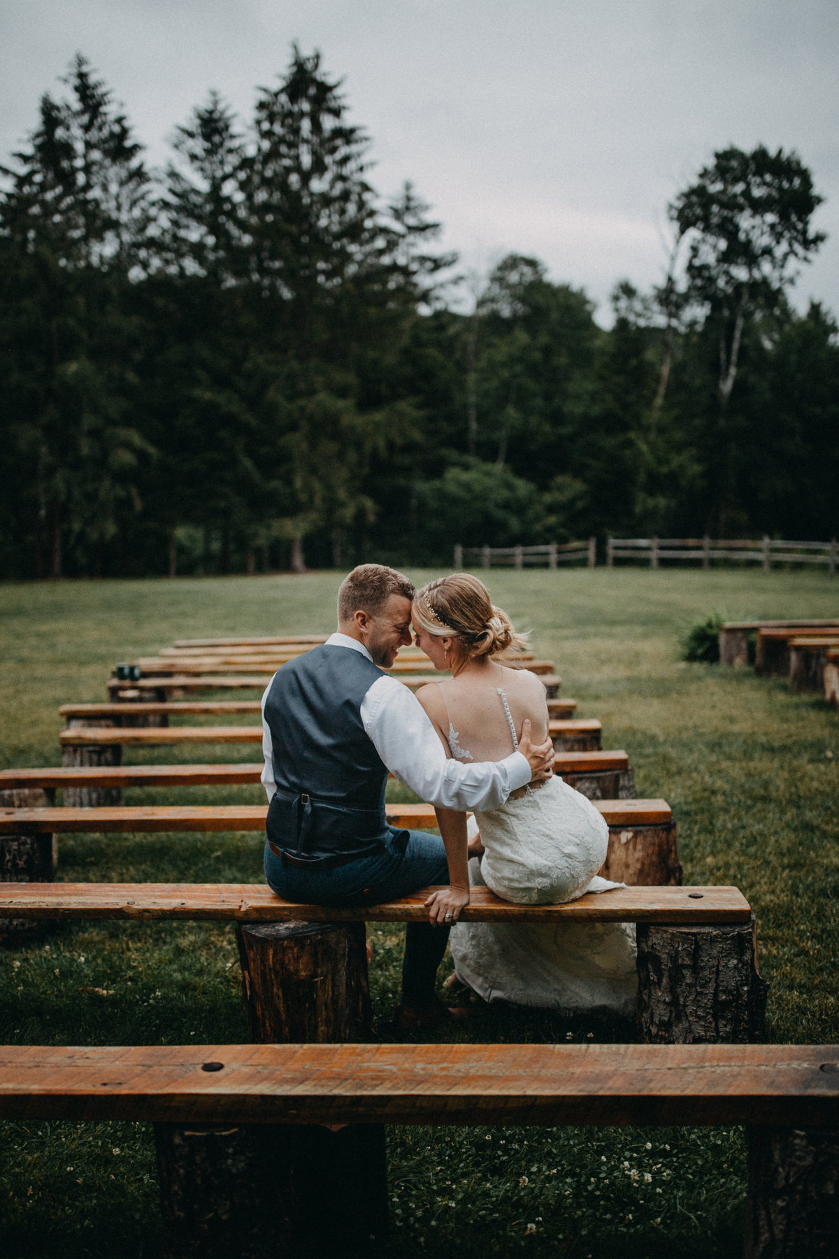 Bride and groom cuddling on bench