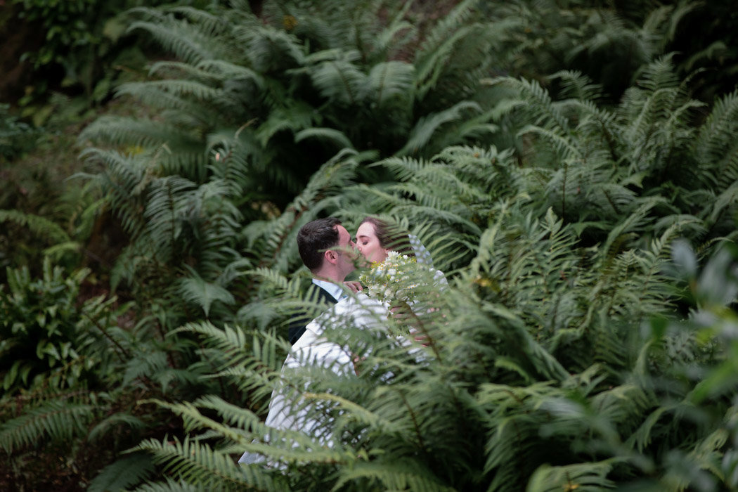 Couple kissing in the undergrowth at
