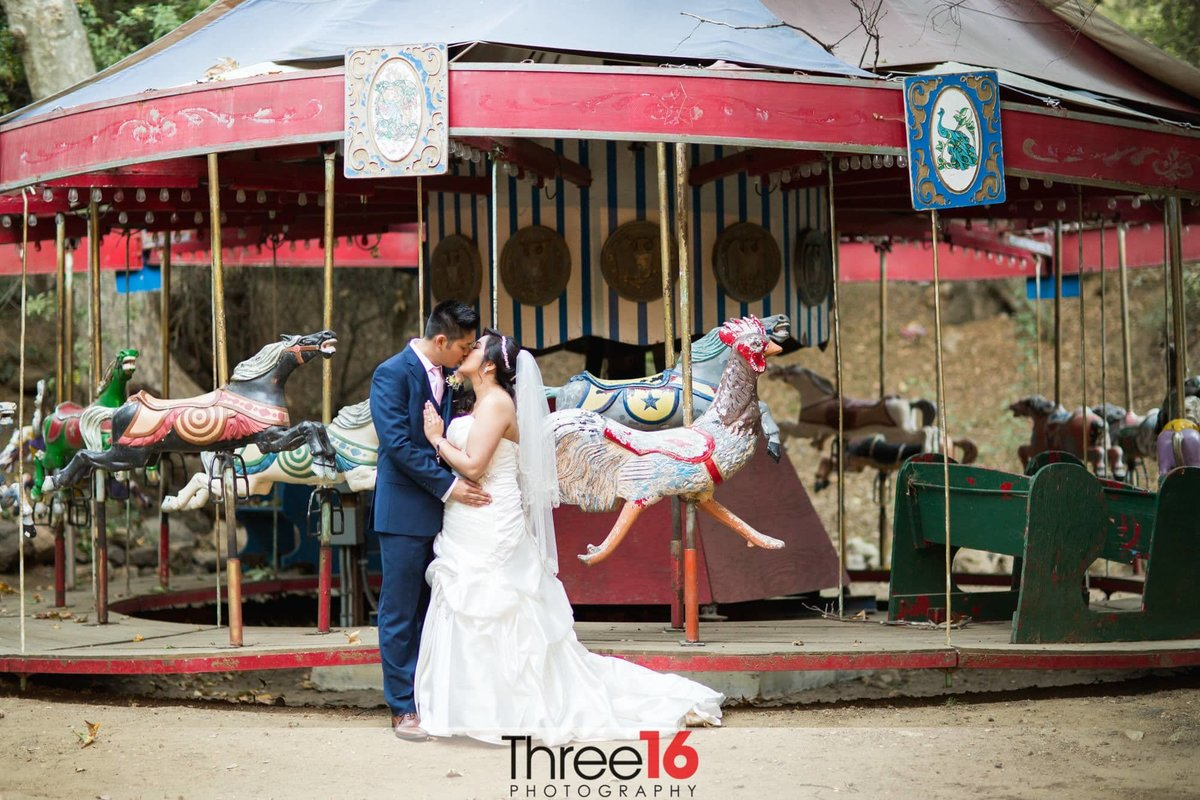 Groom shares a kiss with his Bride in front of a carousel at Calamigos Ranch
