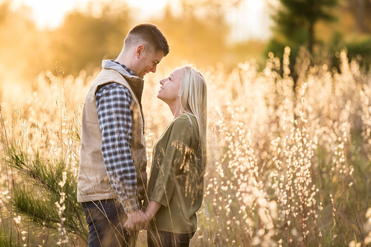 couple photo in a field at sunset golden hour