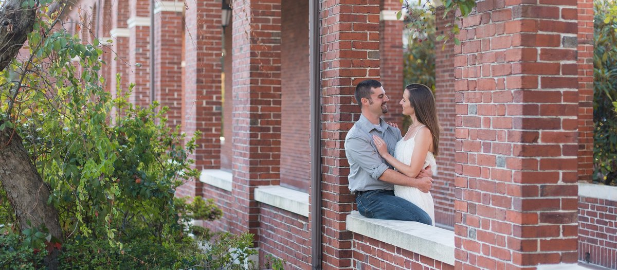 Couple looking at each other in brick arches on Burke Rehabilitation Hospital's campus in White Plains, NY photo