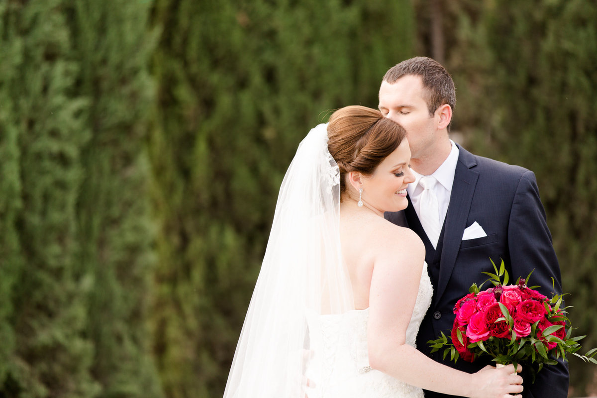 Groom whispers into his brides ear during their bridal photos at villa de amore by matty fran photography