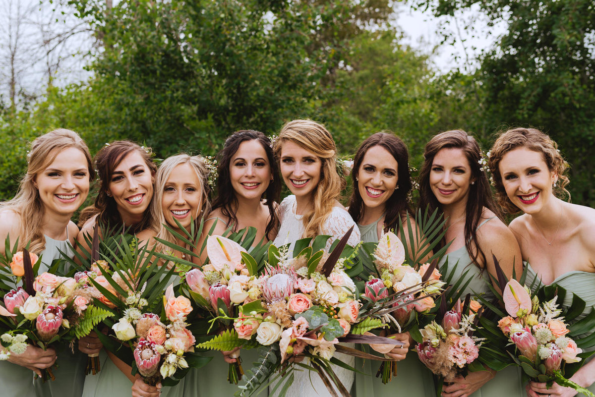 bridesmaids in sage green with wild tropical bouquets