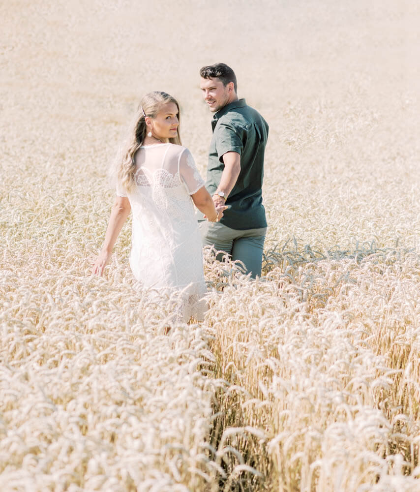 wedding photographer stockholm helloalora engagement shoot walking on a summer meadow