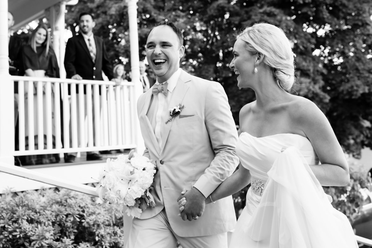 The bride and groom head into their Camden Inn wedding reception laughing while holding hands in Maine