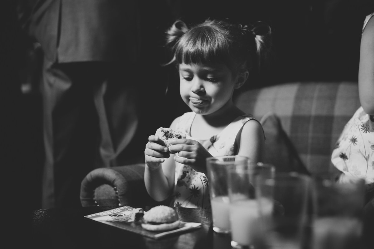 girl eating mini burger at wedding
