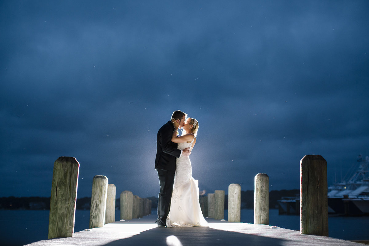 bride and groom kissing on dock at night at clarks landing yacht club wedding