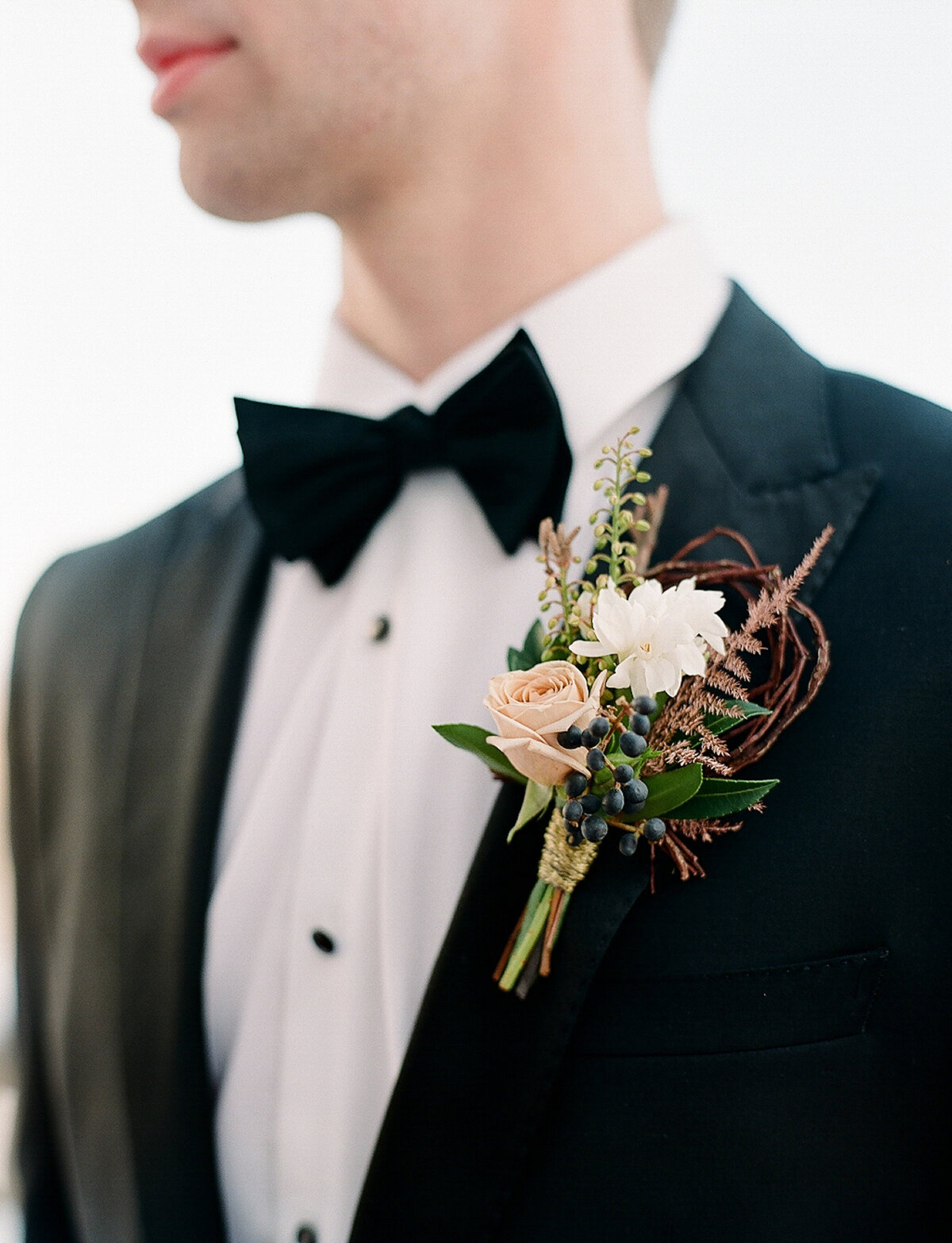 Groom wearing tuxedo and boutonniere at wedding