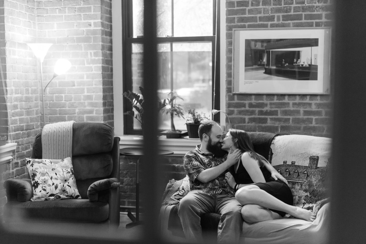 couple cuddling on couch during inhome engagement session by richmond virginia photographer