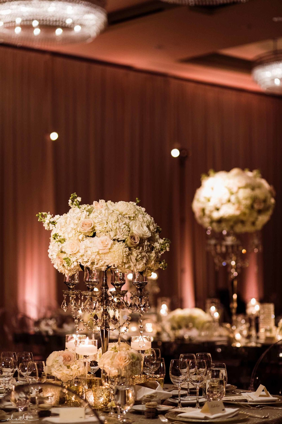 White stock, roses, and hydrangea make up these tall floral centerpieces.