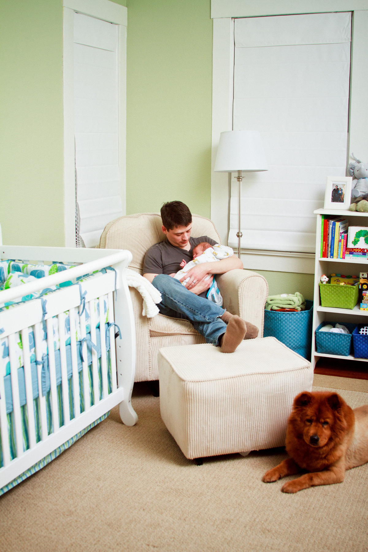 In home newborn photography session in San Antonio with Father, son, and dog in the nursery.