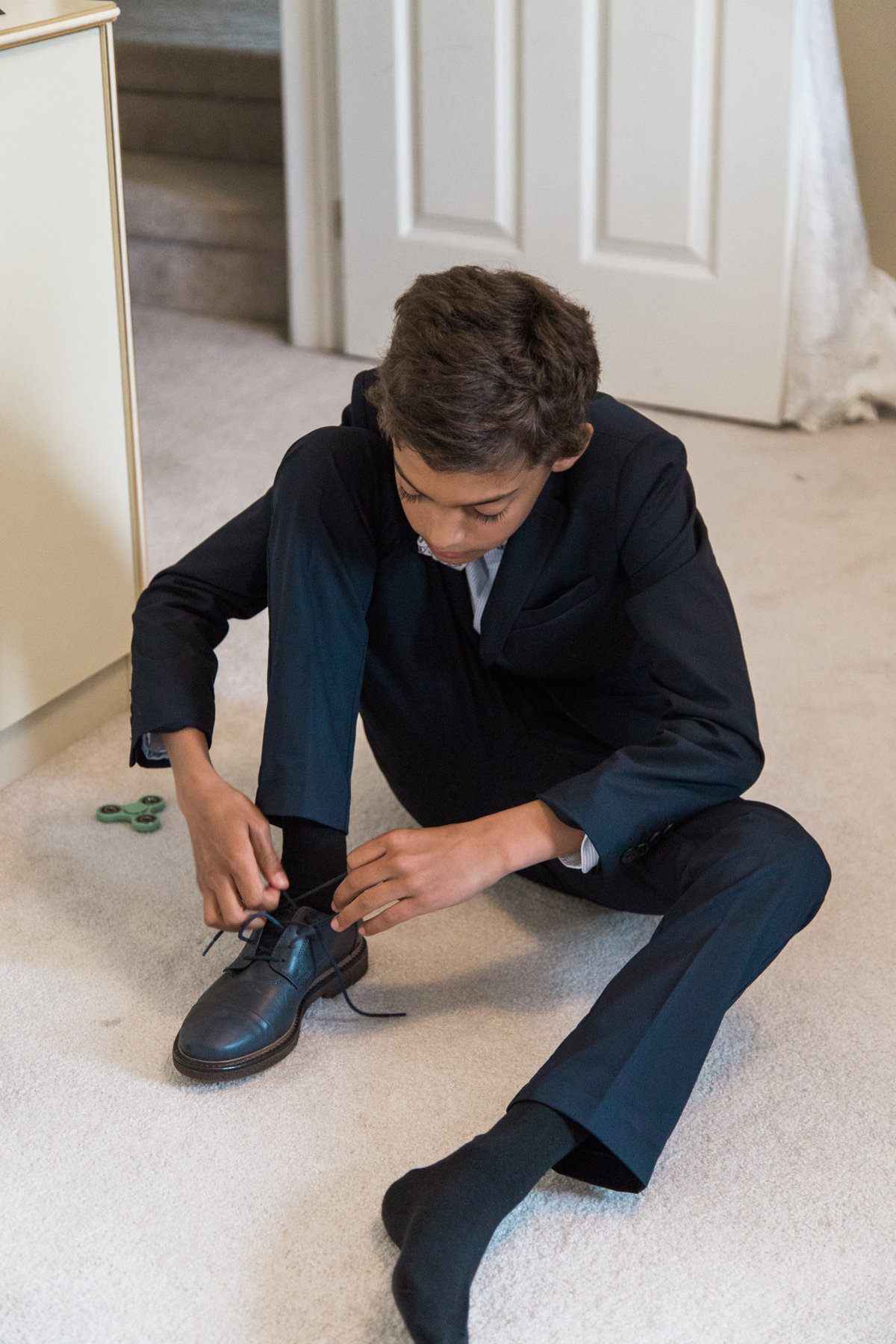 Brides son putting on his shoes