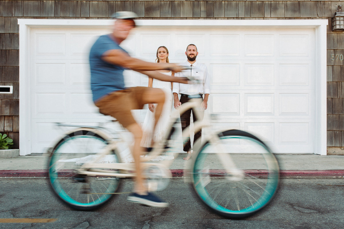 Bride & groom pose as a beach cruiser passerby looks on during their portraits in Newport Beach, Ca.