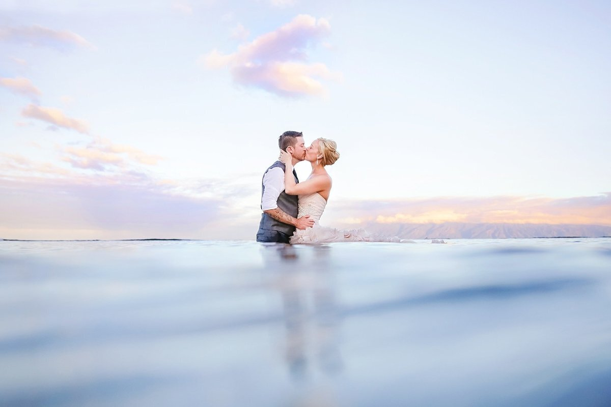 Trash the dress Maui portrait with bride and groom kissing in the ocean