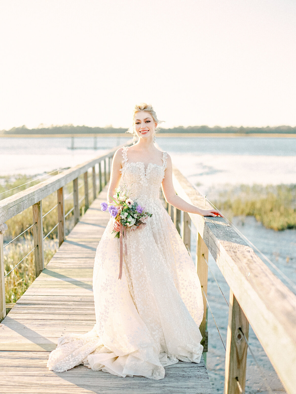 Bride with purple floral bouquet smiling on wooden dock on river at Charleston Wedding
