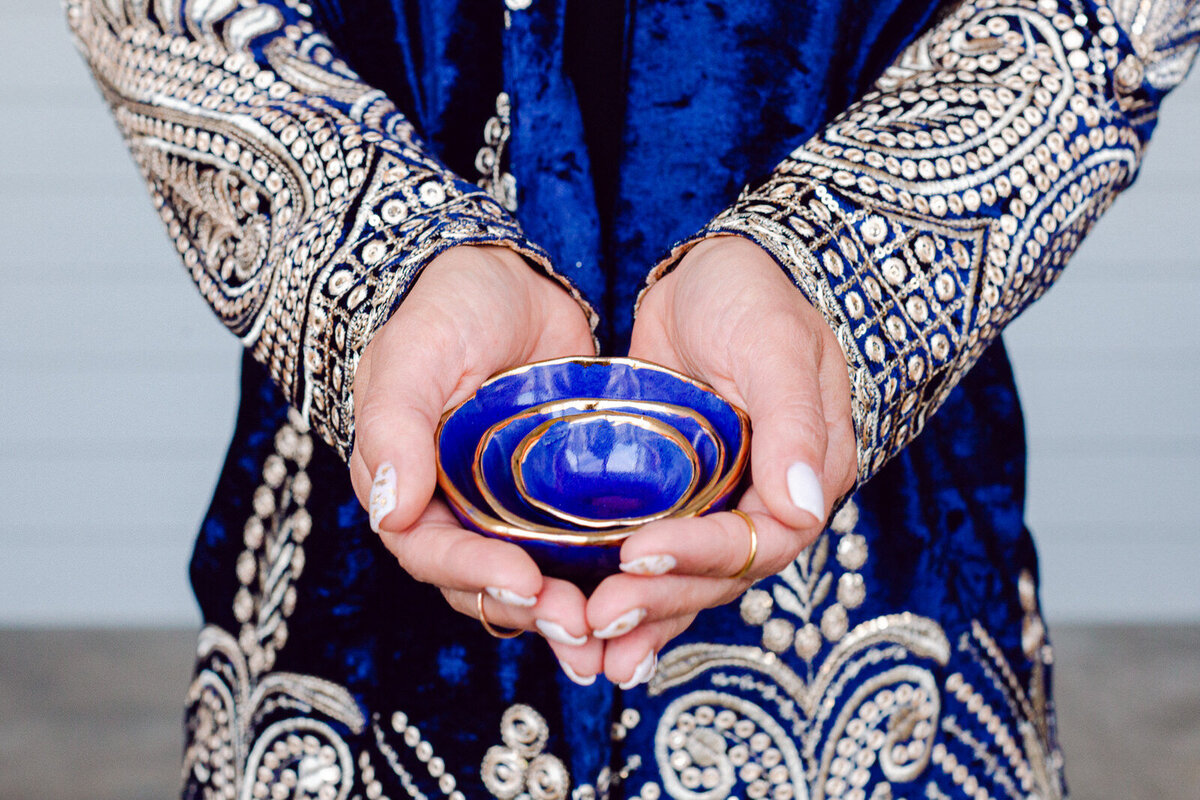 girl holding nesting bowls in blue arabian coat