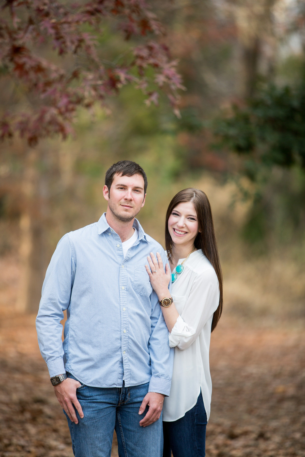 Engagement session of couple standing in clearing covered in leaves during the fall.