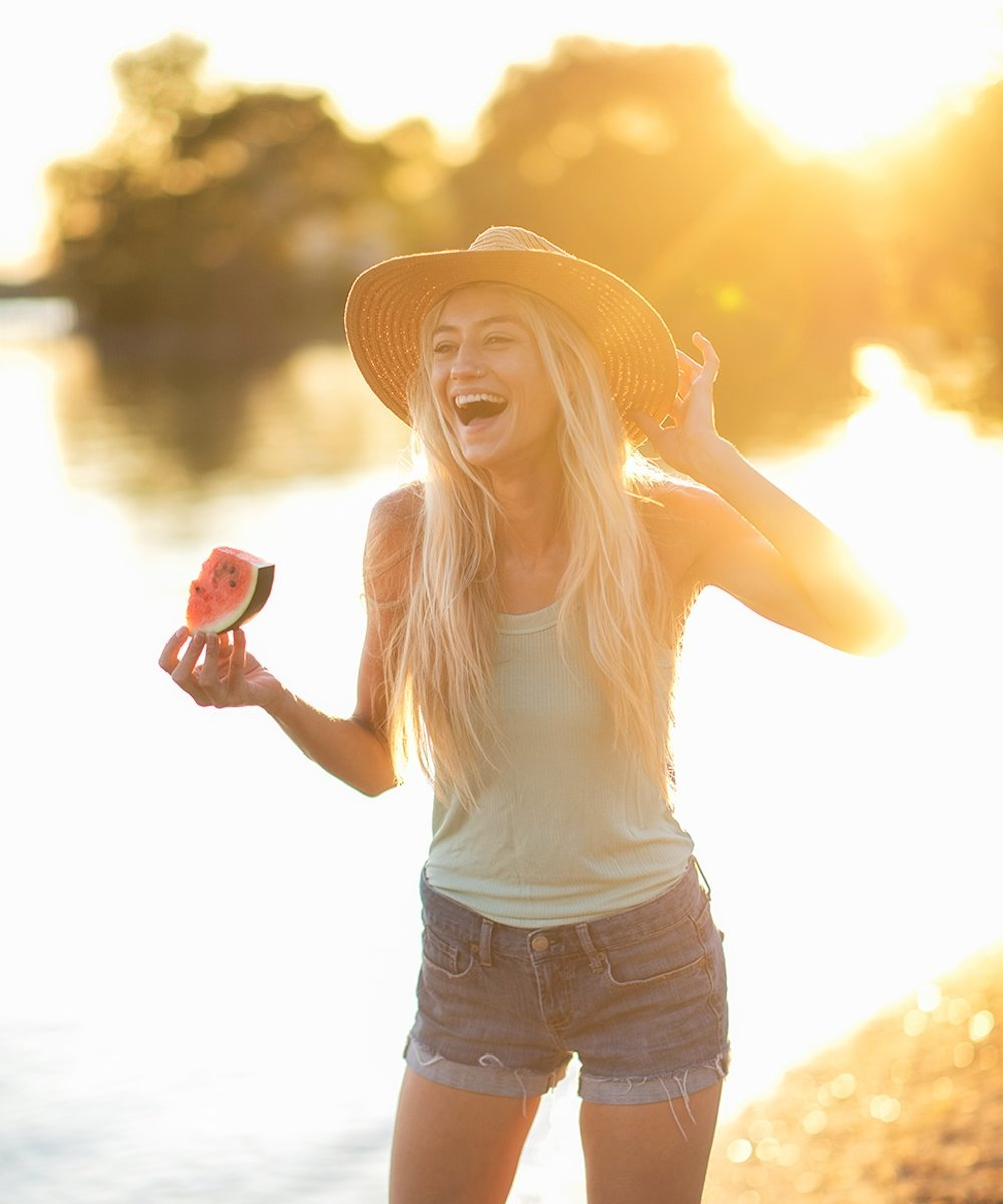 woman on beach holding a slice of watermelon and laughing