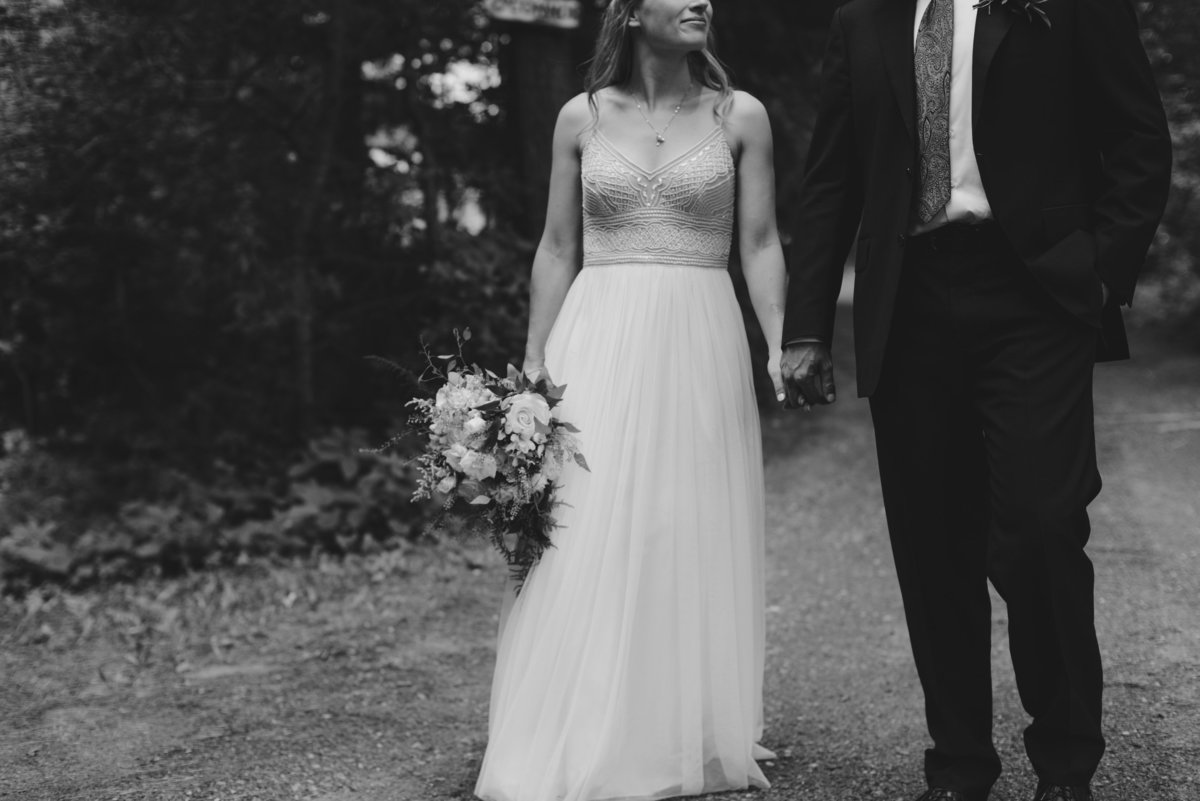 Bride and groom holding hands walking along dirt road in black and white
