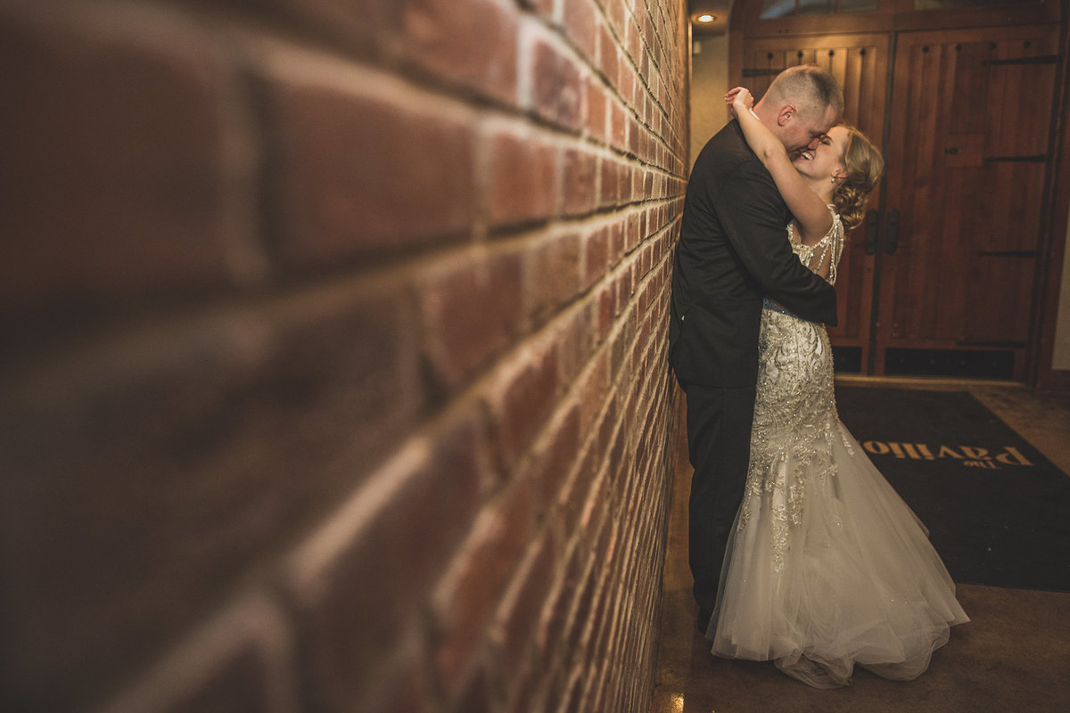 bride and groom kissing in hallway right after their wedding