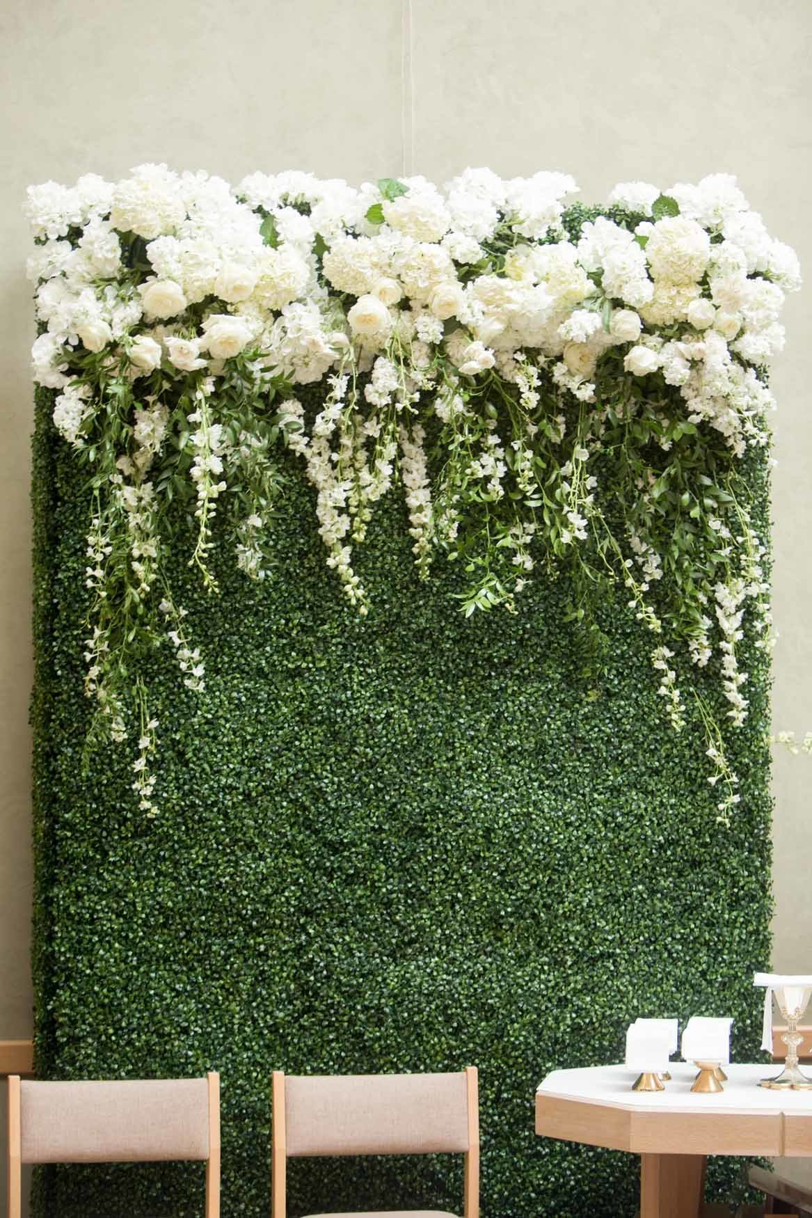 Wedding ceremony alter greenery wall with white flowers