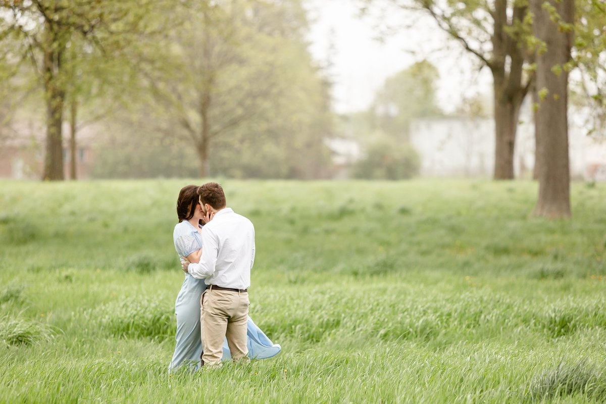 Couple-kissing-in-a-windswept-grassy-field-in-London-Ontario