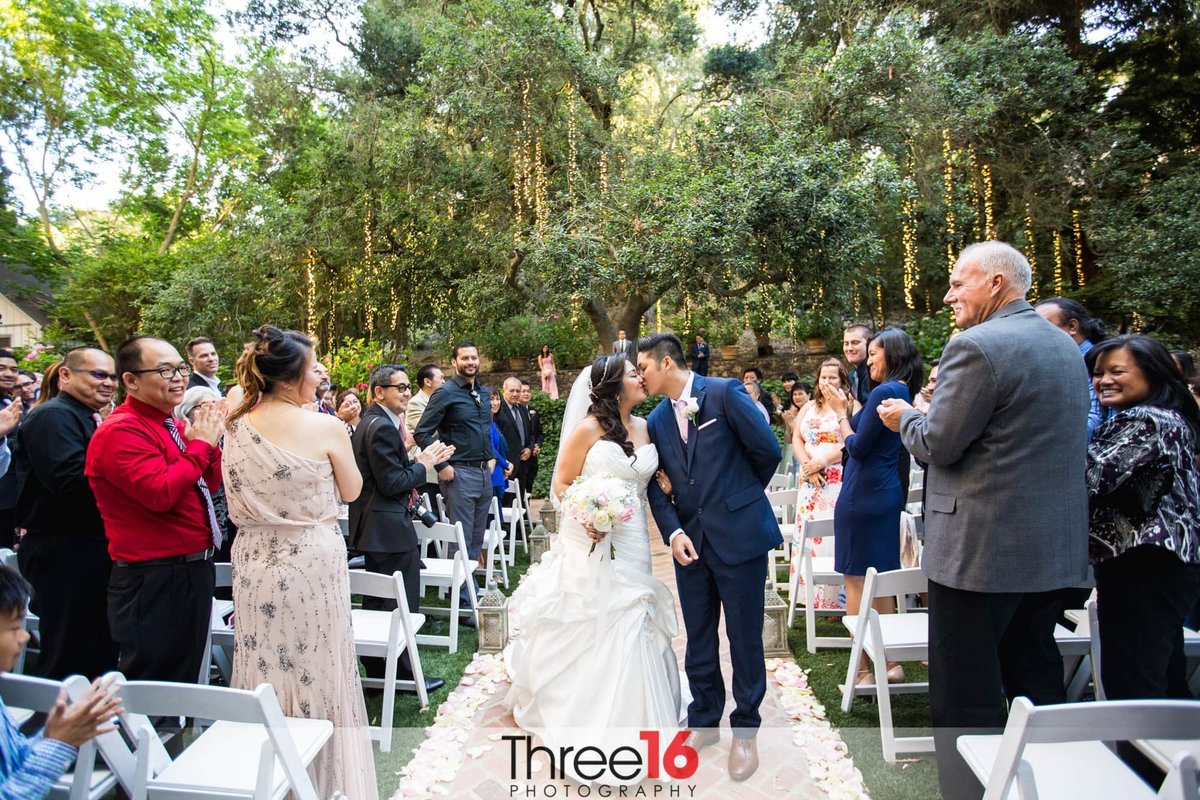 Newly married couple share a kiss at the end of the aisle