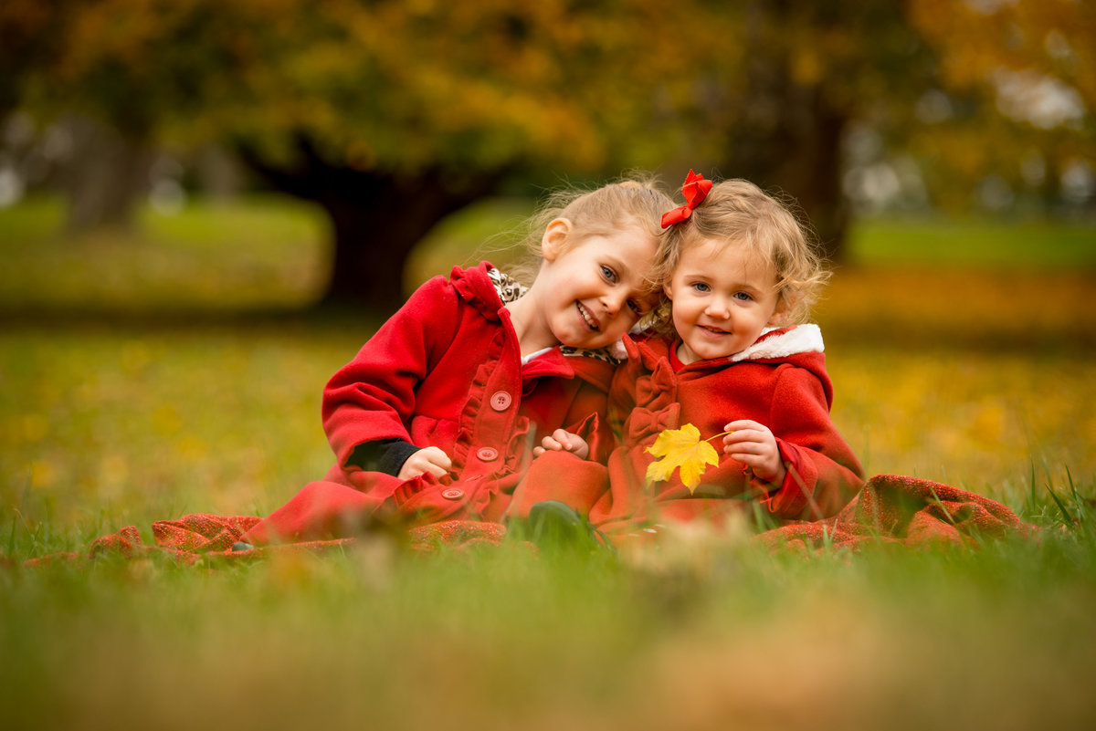 Two sisters enjoy a beautiful outdoor family photo shoot