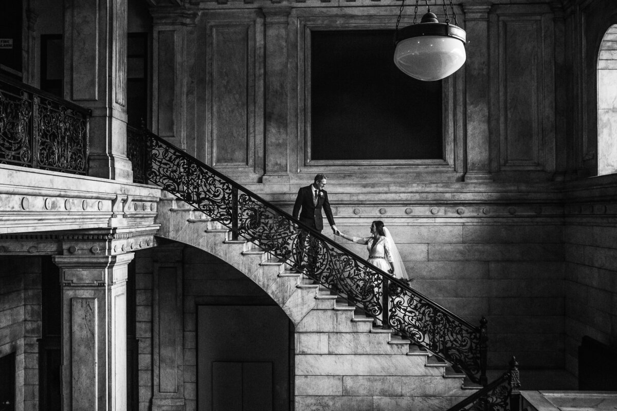 Groom leading Bride up stairwell in Ellicott Development building in Buffalo, New York