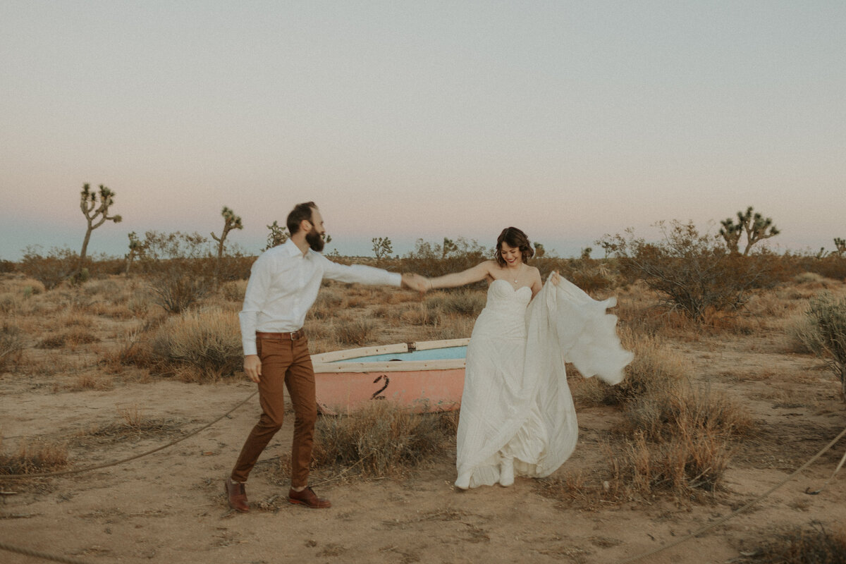 Photo of bride dancing with her groom during sunset in Joshua Tree National park