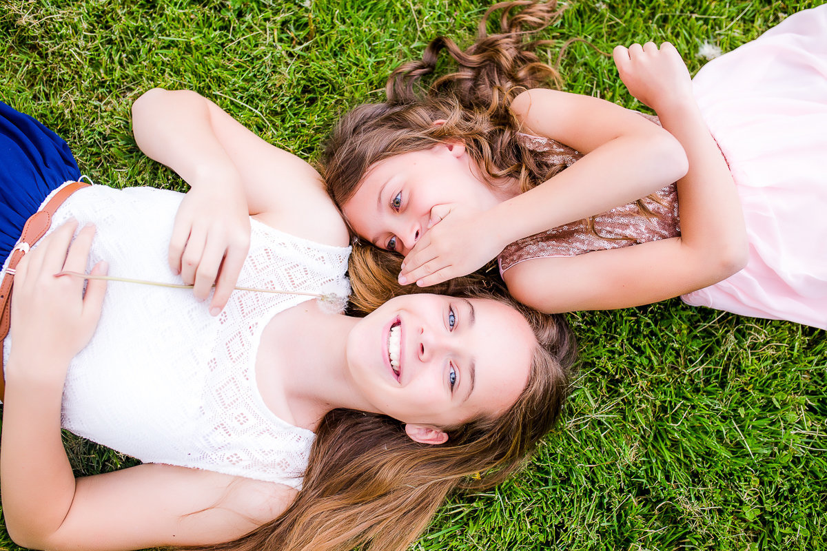 Sisters laying and whispering to each other outdoors {Hamilton Child Photographer}