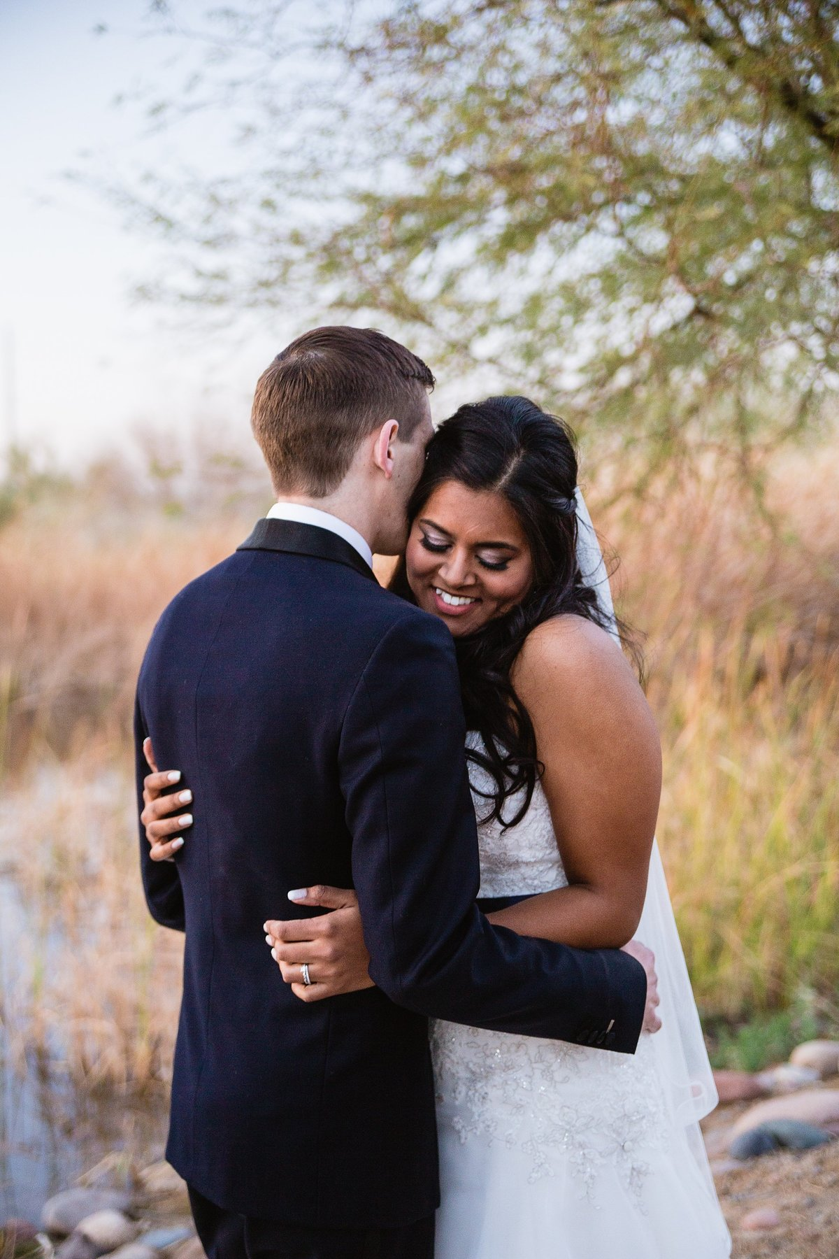 Happy bride sharing an intimate moment with her groom by Phoenix wedding photographer PMA Photography.