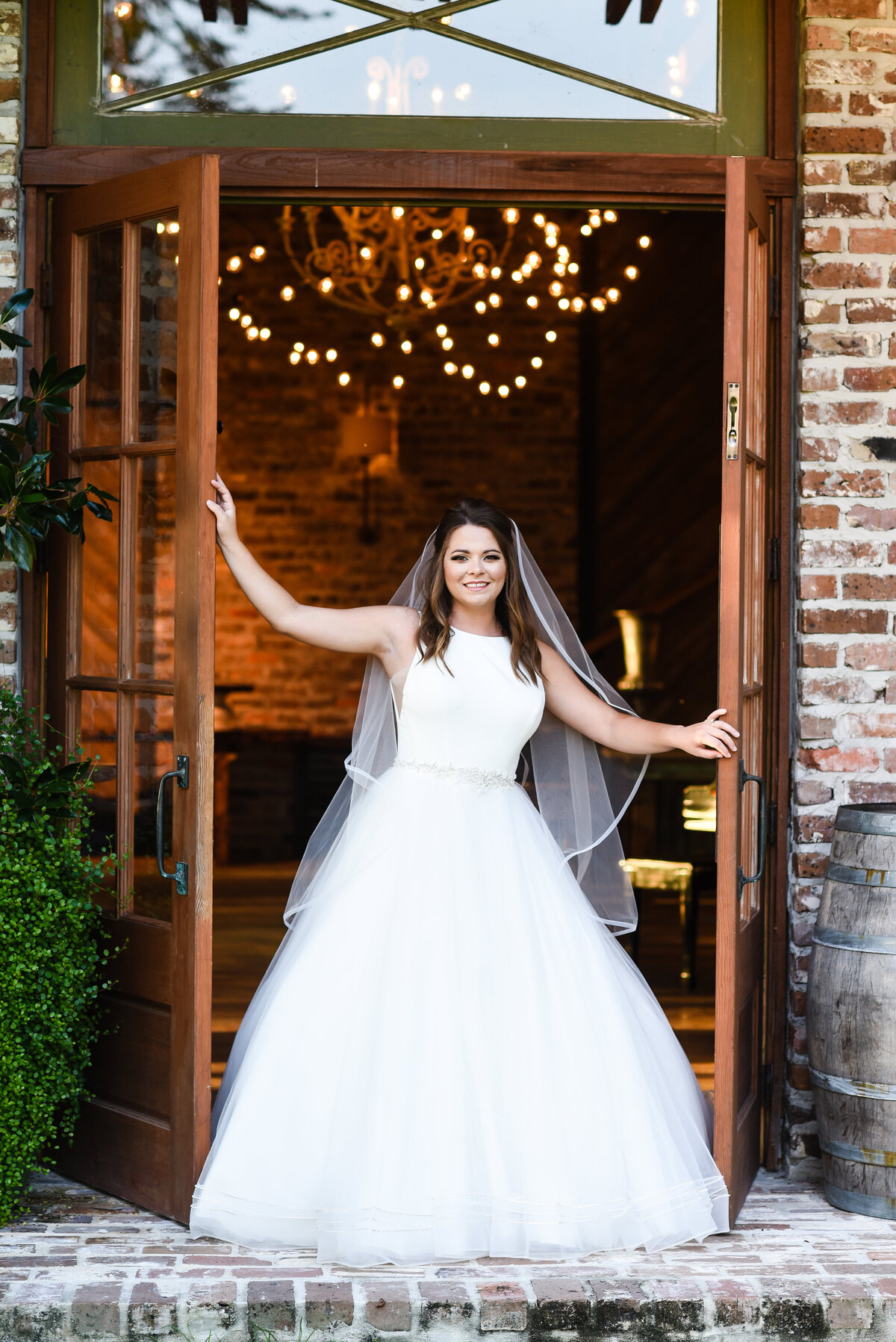 Beautiful bridal portrait photography: bride stands in between french doors at Green Gates Farmhouse venue in Mississippi