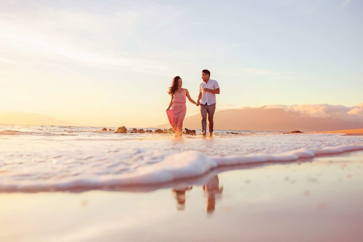 Couple holds hands and runs toward the camera at sunset on the beach