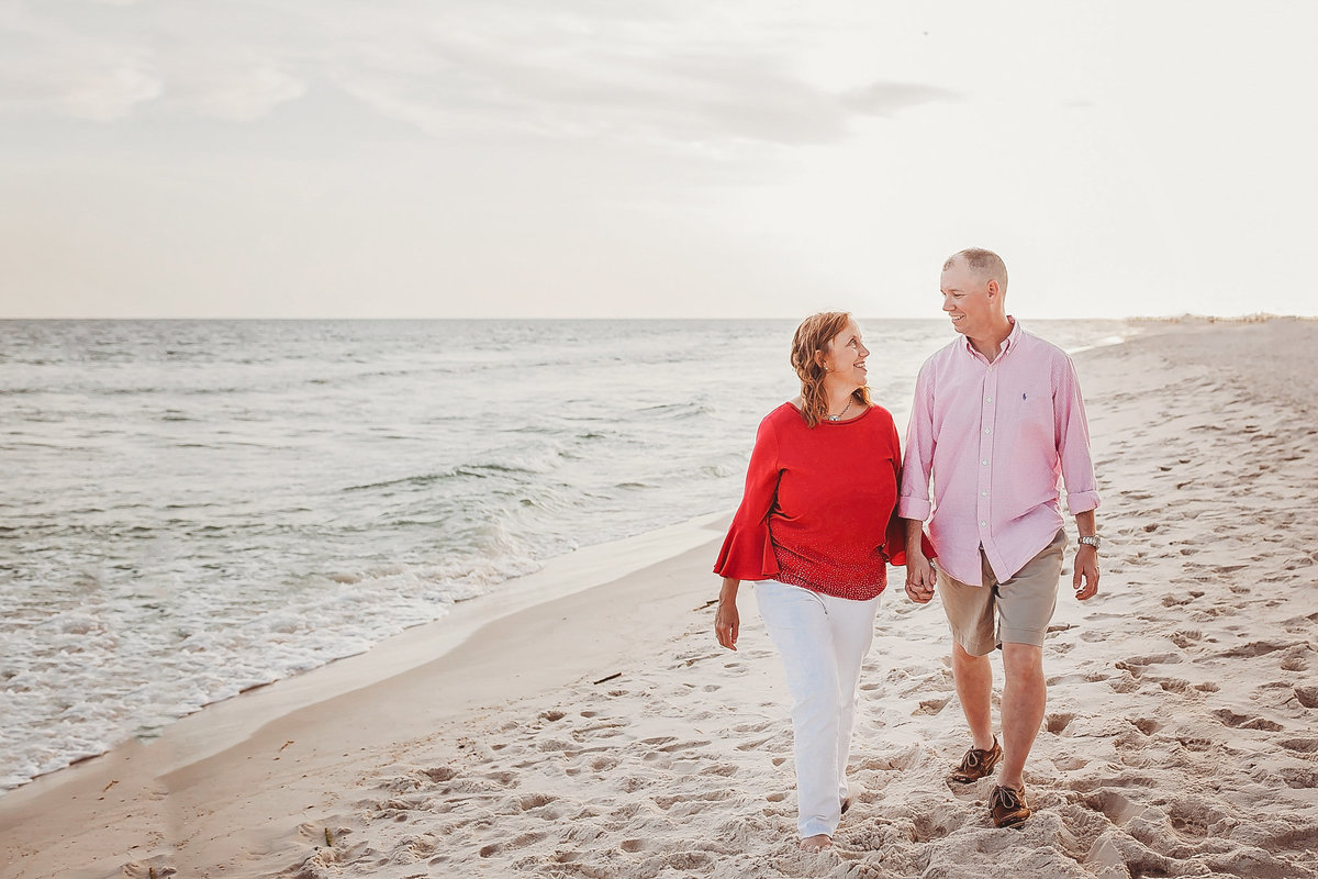 Couple laugh and hold hands, walk along beach
