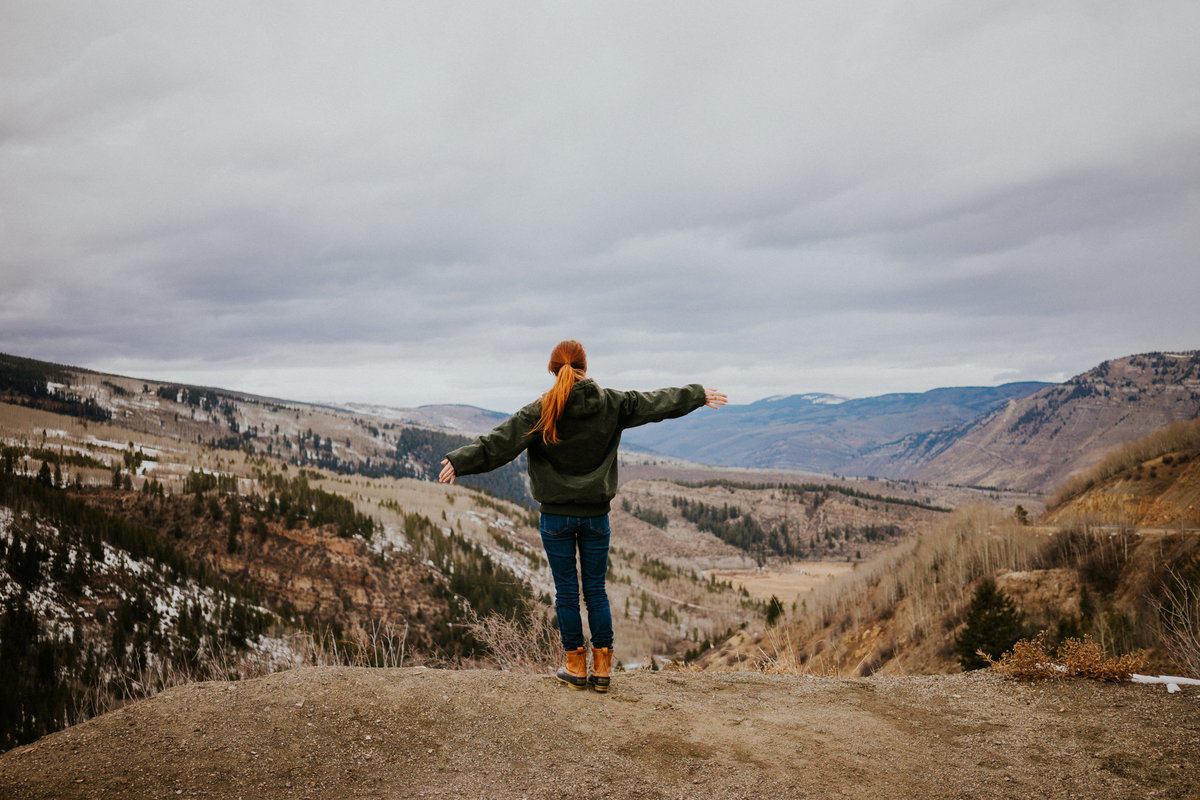 Alexandria Salmieri stands on a ledge facing Rocky Mountains of Vail and Silverthorne Colorado  with arms outstretched