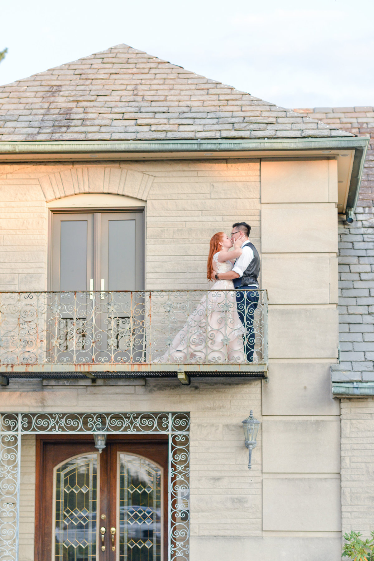 Bride and groom share a kiss on the balcony at Deer Park Manor in Bloomington, Indiana