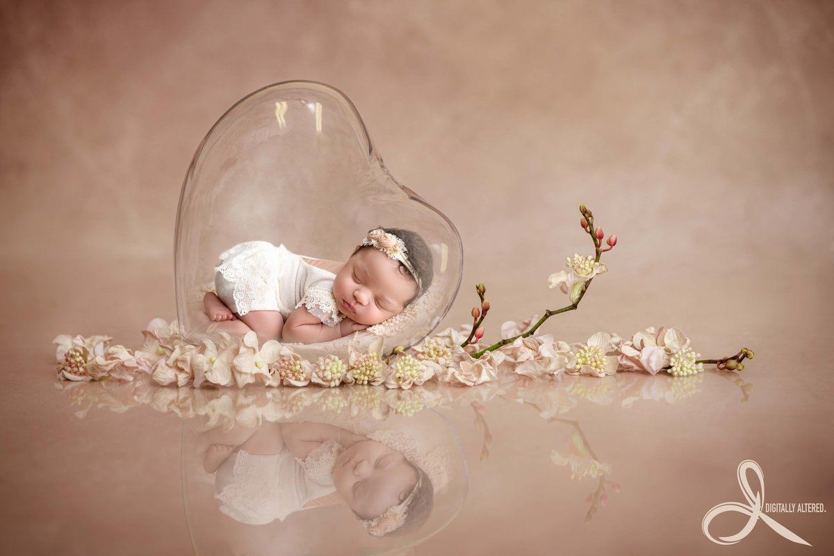 Newborn girl in a heart made out of glass