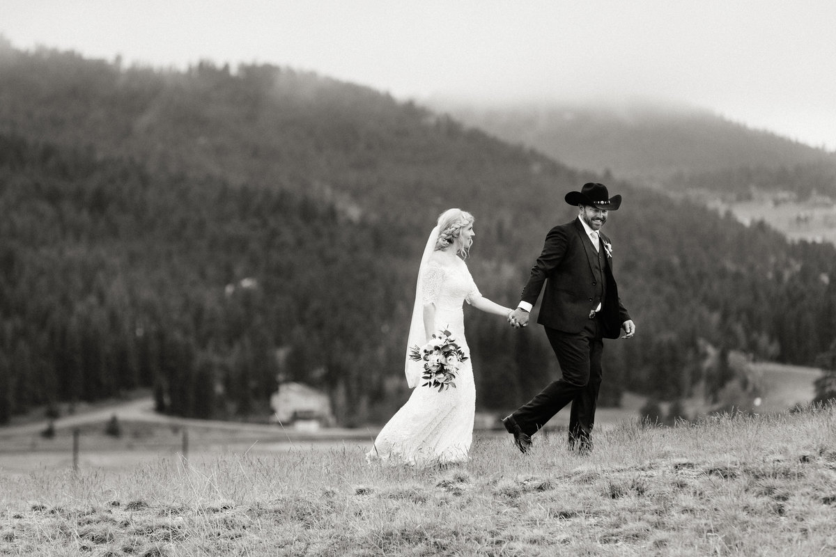 A newly married couple walk up a hill.