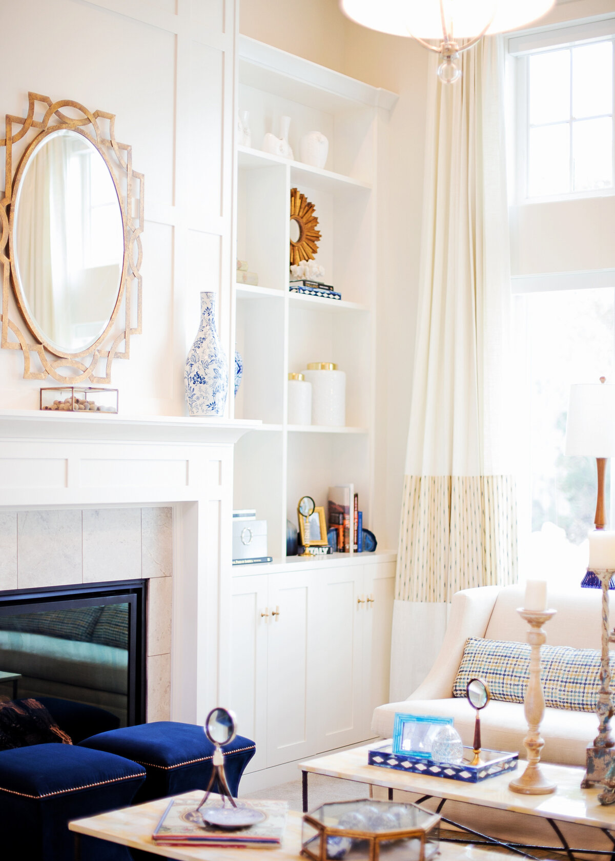 A white painted sitting room has royal blue velvet stools in front of the fireplace, with a gold mirror above it.