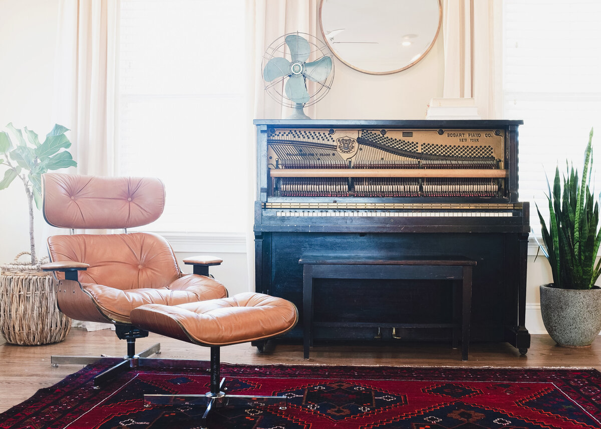 A stripped vintage piano is pictured by a red Turkish rug with a modern leather chair.