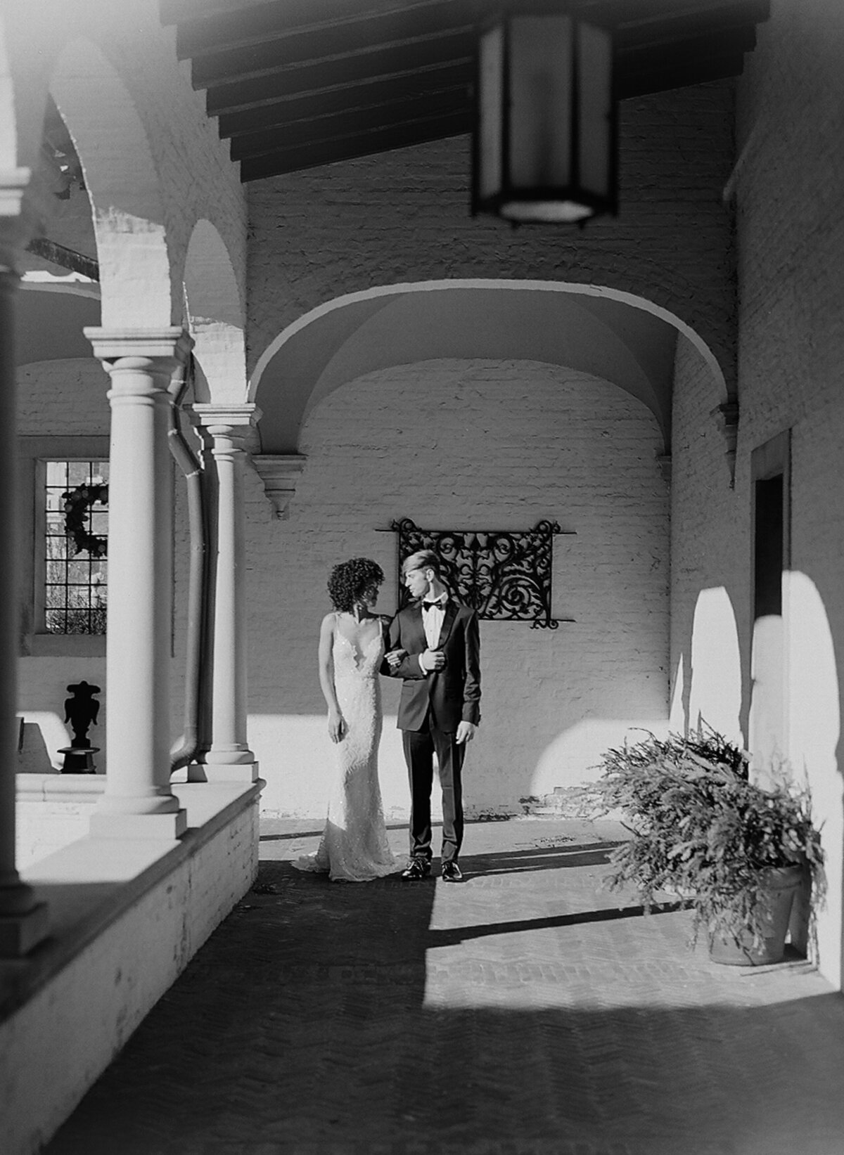 Black and white photo of bride and groom walking in Italian villa courtyard