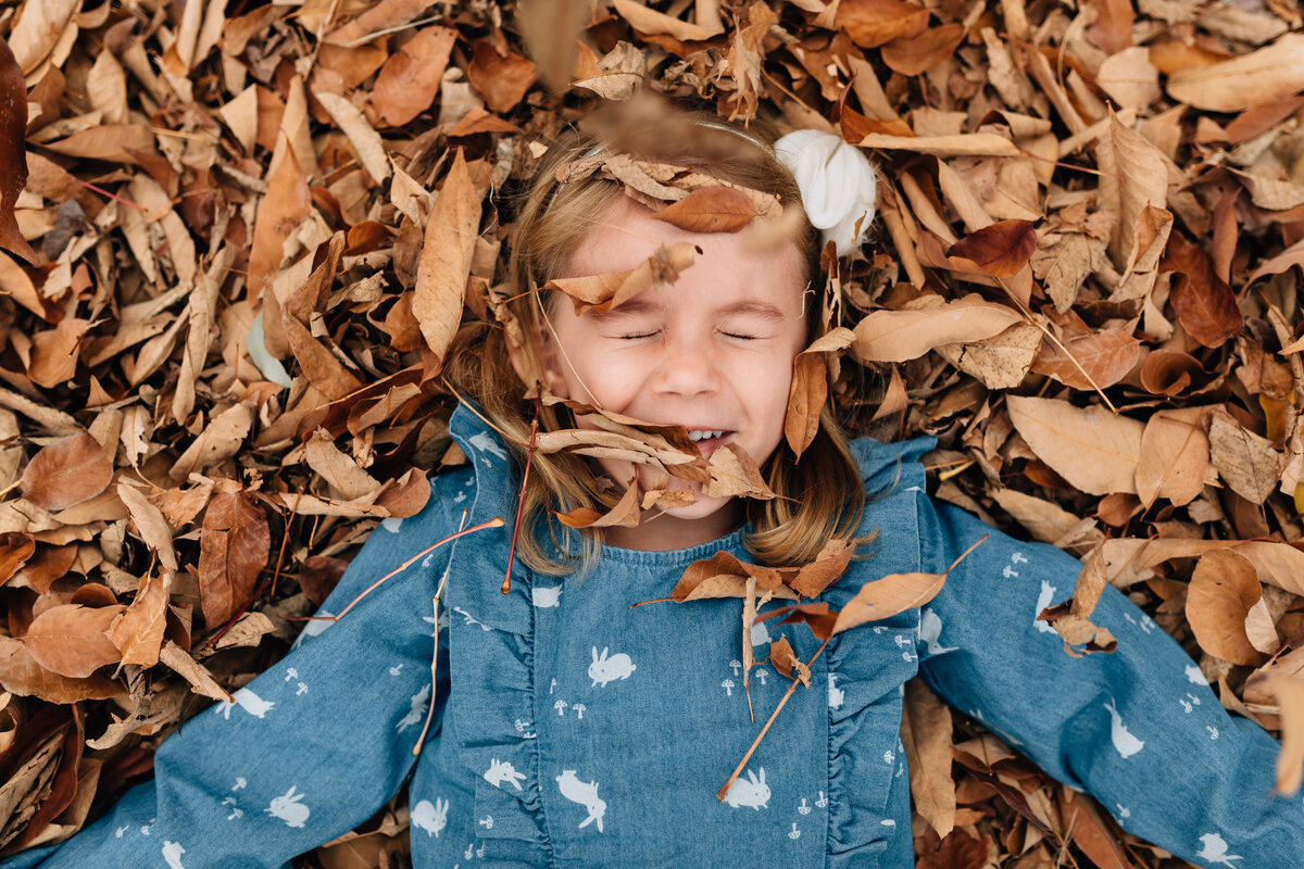 girl in autumn leaves natural outdoor Melbourne family photography And So I Don't Forget Photography