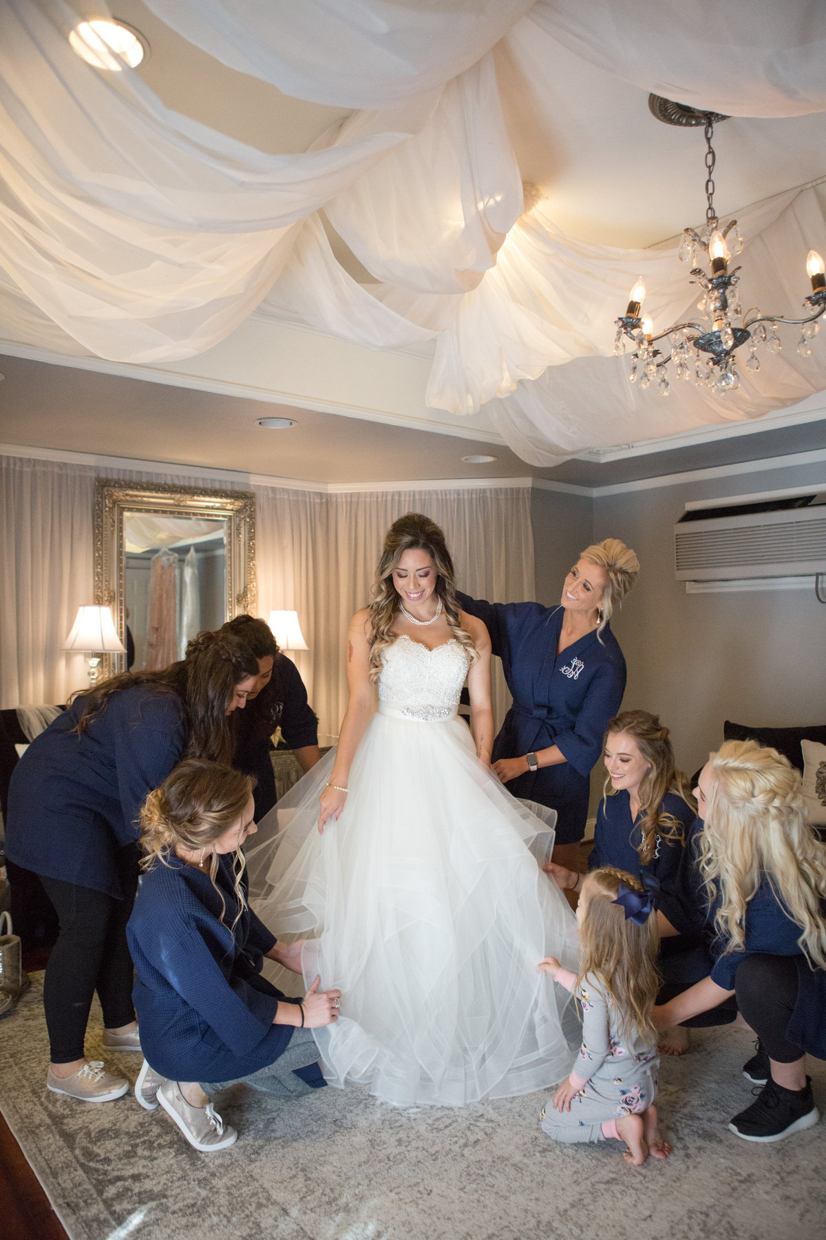 bridesmaids in robes helping bride get ready