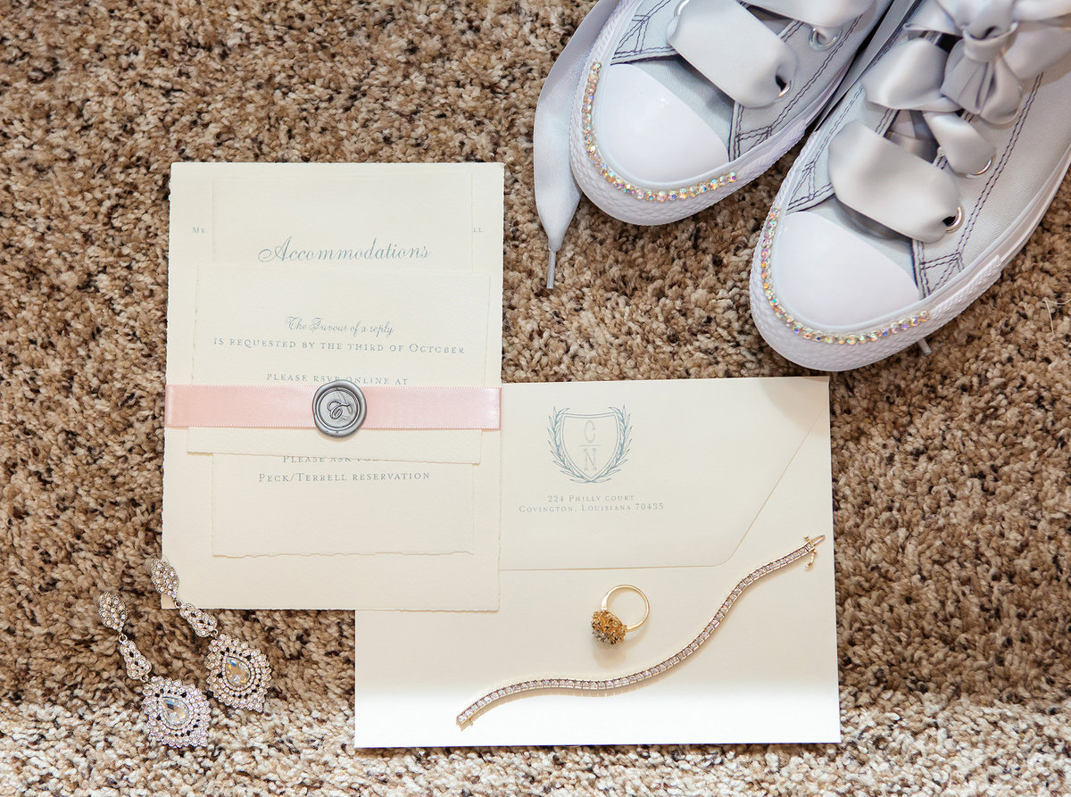 wedding invitation, wedding shoes and wedding jewelry on carpet at the Fleur de Lis Event Center