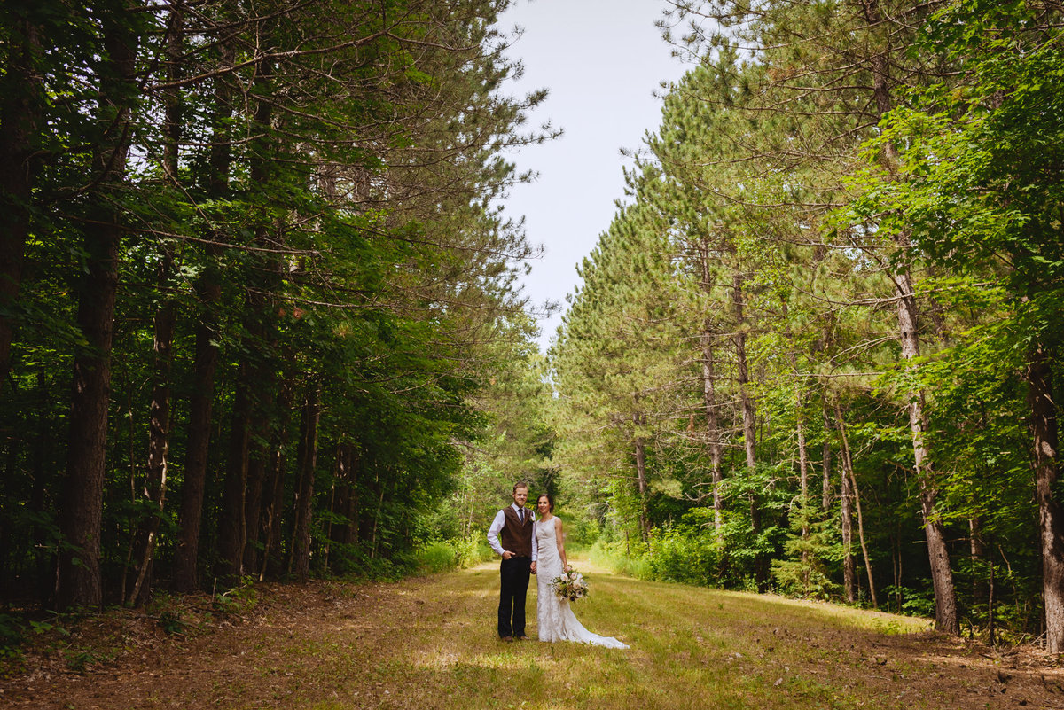 bride and groom standing on a path in the woods surrounded by trees